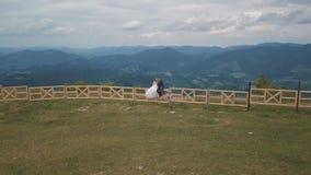 Выхольте с невестой сидите на загородке около холмов горы Воздушная съемка трутня сток-видео