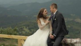 Выхольте с невестой сидите на загородке около холмов горы r r акции видеоматериалы