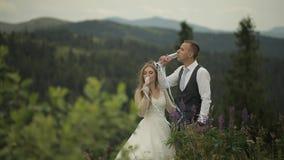 Выхольте с шампанским напитка невесты на холмах горы r r сток-видео