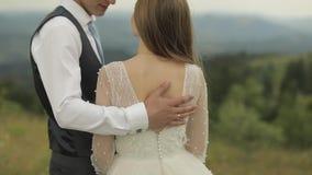 Выхольте штрихует заднюю часть невесты около холмов горы r акции видеоматериалы