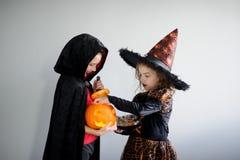 выходка обслуживания Мальчик и девушка в костюмах на хеллоуин Стоковые Фото