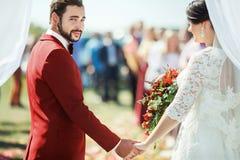 Выхольте остроконечно смотреть камеру пока стоящ в своде свадебной церемонии с рукой невесты на предпосылке толпы стоковые фотографии rf