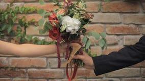 Выхольте руки над букетом к невесте против предпосылки кирпичной стены сток-видео