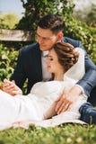 Выхольте смотреть на кольце невесты которое кладущ на ноги groom Стоковое Изображение RF