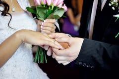 Выхольте установку на свадебную церемонию для кольца золота невесты на пальце Стоковые Фотографии RF