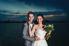 Выхольте embrecing невесту на речном береге на ноче Стоковая Фотография
