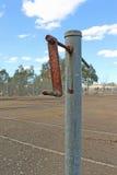 Вышедший из употребления теннисный корт асфальта и ржавый сетчатый столб Стоковые Изображения RF