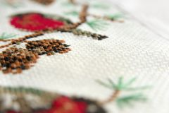 Вышивка вышивки крестиком Красный bullfinch на конце макроса вышивки ели вверх Стоковая Фотография RF