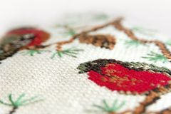 Вышивка вышивки крестиком Красный bullfinch на конце макроса вышивки ели вверх Стоковая Фотография