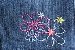 Продетые нитку цветки на джинсыах Стоковая Фотография