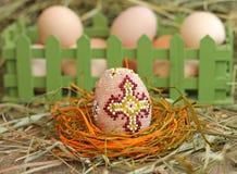Вышитый бисером пасхальное яйцо на предпосылке сена Стоковое Изображение RF