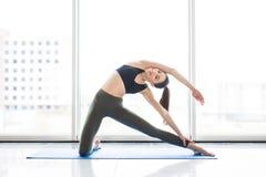 Выдвинутый треугольник Молодая красивая йога женщины представляя на панорамной предпосылке города окон Стоковое Фото