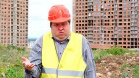 Вы глупый построитель стучая его кулаком на главных стойках на предпосылке строительной площадки акции видеоматериалы