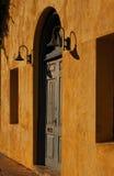 Выдержанная голубая дверь в желтой стене Стоковые Изображения
