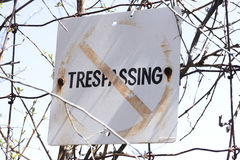 Выдержанный крупный план старой и отсутствие trespassing знака вывешенного к проводу Стоковые Фото