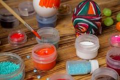 Выдержите щетку в краске, чонсервных банках на деревянной таблице, пасхальных яйцах Стоковое Изображение RF