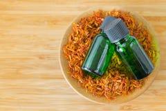 Выдержка масла концентрата чисто сафлора необходимая в зеленой бутылке Стоковая Фотография