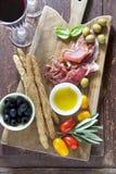 Вылеченное мясо на деревянной разделочной доске с красными томатами, оливками a Стоковое Фото