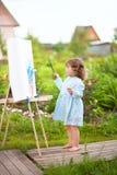 Вылечите краски девушки малыша на мольберте в саде Стоковые Изображения