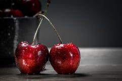Выделяют свежие вишни в красном цвете на серой предпосылке Стоковые Фото