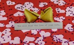` Вы найдете влюбленность вашего сообщения ` жизни в сломленном печенье с предсказанием на красной предпосылке покрытой с Хартами Стоковое Изображение RF