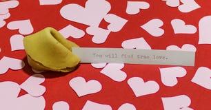 ` Вы найдете истинное сообщение ` влюбленности в печенье с предсказанием на красной предпосылке покрытой с Хартами Стоковая Фотография RF