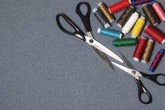Вьюрки потоков других цветов на серой сплетенной предпосылке 2 пары ножниц различных размеров Стоковое Изображение