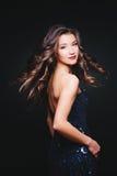 Вьющиеся волосы летания Женщина с совершенными стилем причёсок и составом в платье с яркими блесками Торжество стоковые фото