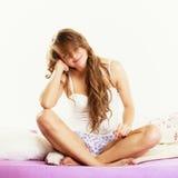 Вьющиеся волосы женщины длинное ослабляя на кровати на утре Стоковые Фото