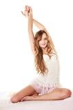 Вьющиеся волосы женщины длинное протягивая на кровати на утре Стоковые Изображения RF