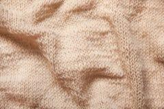 Вяжущ коричневую или бежевую текстурированную предпосылку шерстей, конец вверх сморщенной ткани Стоковое Фото