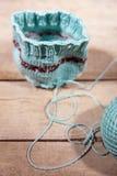 Вязание крючком мастерской и вязать, голубые грелка чашки и пряжа Стоковое Изображение