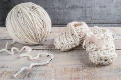 Вязать добычи младенца с bege yarn на деревянном столе Стоковые Изображения RF