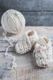 Вязать добычи младенца с bege yarn на деревянном столе Стоковое фото RF