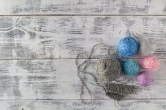 Вязать иглы и пряжа на деревянной предпосылке/естественных шерстях вяжут Стоковое фото RF
