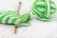 Вязать картина зеленой пряжи на деревянных иглах и пасме Стоковые Изображения