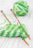Вязать картина зеленой пряжи на деревянных иглах на деревянном bac Стоковое фото RF