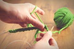 Вязать с зелеными шерстями на деревянном столе Стоковое фото RF