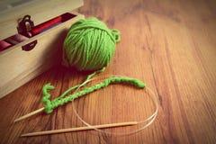 Вязать с зелеными шерстями на деревянном столе Стоковые Фото