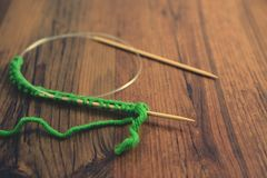 Вязать с зелеными шерстями на деревянном столе Стоковая Фотография