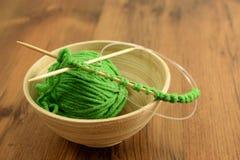 Вязать с зелеными шерстями на деревянном столе Стоковое Фото