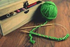 Вязать с зелеными шерстями на деревянном столе Стоковые Изображения RF