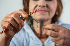 Вязать Элегантные пожилые игла и шерсти удерживания женщины в руке и сделать вязать во время ее отдыха Дама Seniour дальше стоковое фото