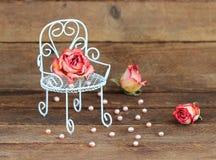 Вянуть розы на кресле и жемчугах на деревянной предпосылке Стоковые Фотографии RF