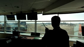 В авиапорте диспетчер службы управления воздушным движением смотрит в расстояние держа радио
