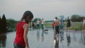 Влажная маленькая девочка стоя играющ при вода, стоя на двигателе фонтана Счастливый ребенок имея потеху в горячем летнем дне видеоматериал