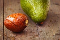 Влажное ядр авокадоа на коричневой деревянной старой таблице Стоковые Изображения RF