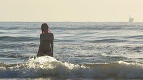 Влажный женский приходить из волн моря видеоматериал