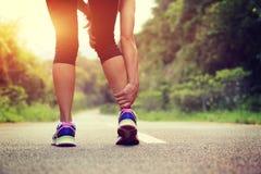 Владение бегуна ее нога спорт раненая Стоковые Изображения