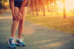 Владение бегуна женщины ее колено спорт раненое Стоковая Фотография RF